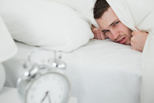Annoyed man covering his ears while his alarm clock is ringing