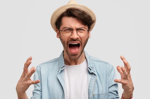 麦わら帽子とデニムシャツを着て、白い壁にポーズをとって、無精ひげでイライラした男の農夫は、怒ってジェスチャーをし、イライラして叫び、収穫に不満を抱いています