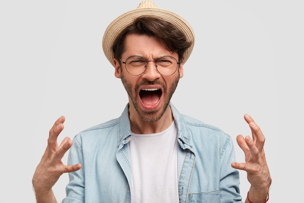 Agricoltore infastidito con stoppie, gesticola con rabbia e grida irritato, insoddisfatto del raccolto, vestito con cappello di paglia e camicia di jeans, posa contro il muro bianco