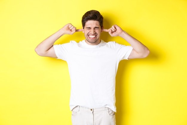 Annoyed man grimacing and shutting ears, complaining on loud noise, standing against yellow background. copy space