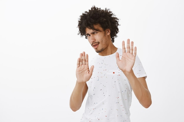 Annoyed man refusing disgusting offer, raising hands in rejection