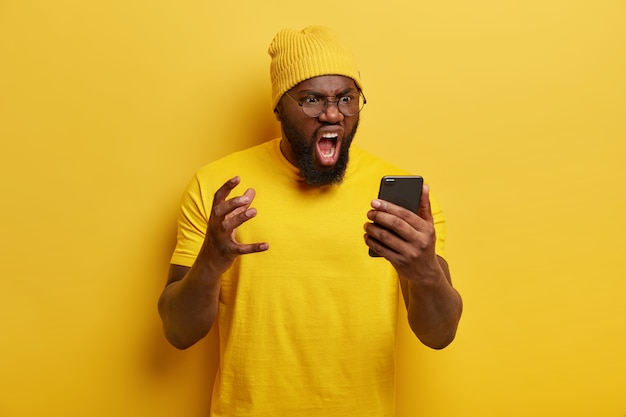 L'uomo infastidito dalla folta barba grida con rabbia, ha un'espressione furiosa del viso, riceve notizie spiacevoli, indossa un cappello e una maglietta gialli vivaci