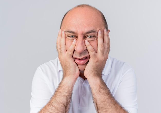 Раздраженный зрелый бизнесмен смотрит вперед и держит руки на лице на белой стене