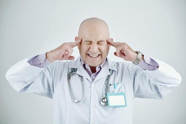 두통, 고립 된 배경으로 고통받는 동안 대머리 머리가 눈을 감고 사원을 만지는 성가신 성숙한 백인 의사