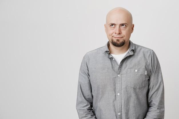 Annoyed middle-aged bald guy roll eyes