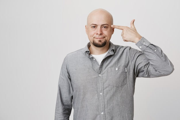 Annoyed middle-aged bald guy shooting himself with finger gun gesture
