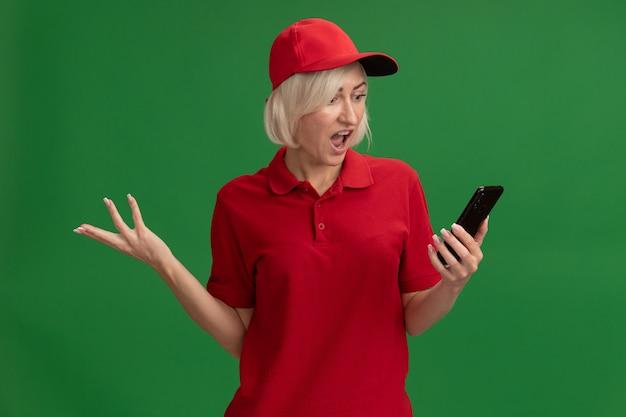 Donna di consegna bionda di mezza età infastidita in uniforme rossa e berretto che tiene e guarda il telefono cellulare che mostra la mano vuota isolata sulla parete verde