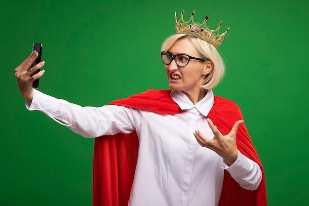 Donna bionda di mezza età infastidita del supereroe in mantello rosso con gli occhiali e la corona che tiene la mano in aria prendendo selfie isolato sulla parete verde