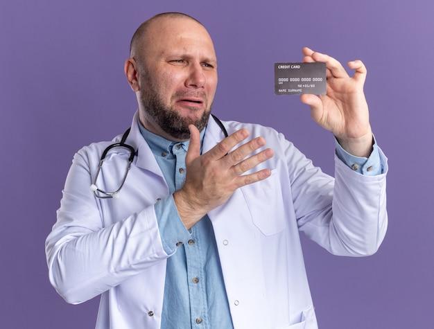 医療用ローブと聴診器を身に着けて、それを指しているクレジットカードを持って見ているイライラした中年男性医師