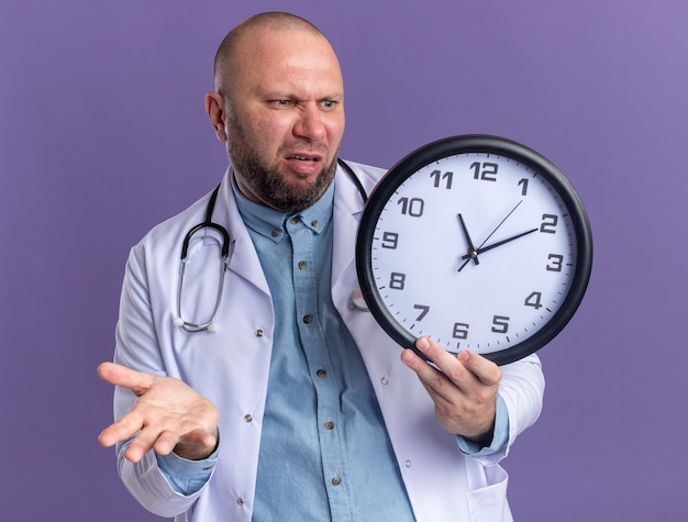 Medico maschio di mezza età infastidito che indossa abito medico e stetoscopio che tiene e guarda l'orologio che mostra la mano vuota isolata sulla parete viola