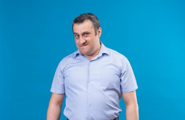 Раздраженный мужчина средних лет в синей рубашке смотрит в камеру с недовольным выражением лица на синем пространстве