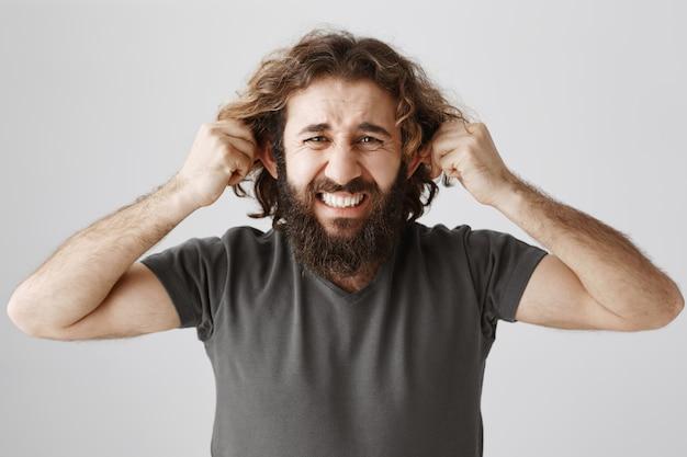 腹が立つ中東の男性が大きな騒々しい騒音から耳をふさいだ