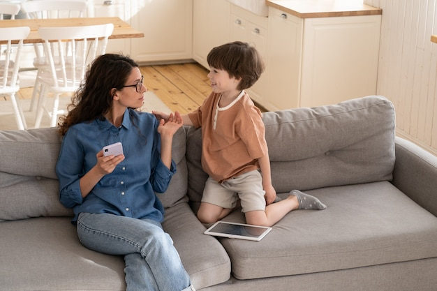 Annoyed mother businesswoman or social media addict scold son for disturbing from using smartphone