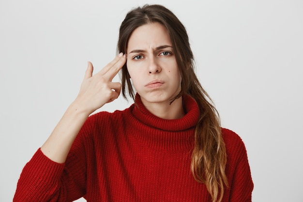 Раздраженная или скучающая девушка делает жест пистолета