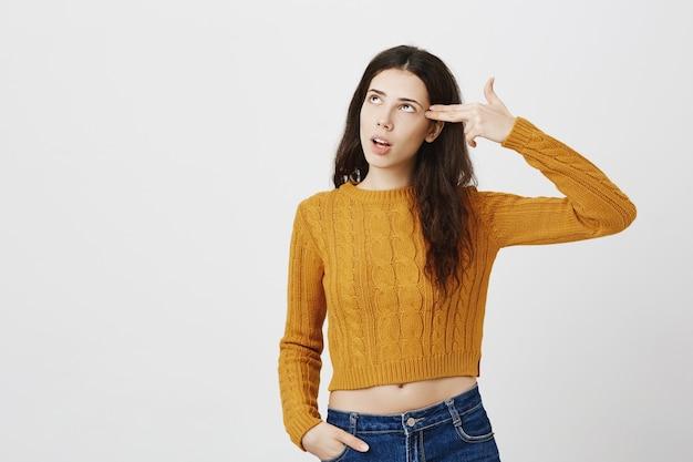 Раздраженная или обеспокоенная девушка закатывает глаза и делает жест стрельбы из пистолета над головой