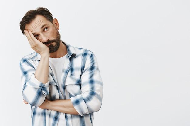 Раздраженный или усталый бородатый зрелый мужчина позирует