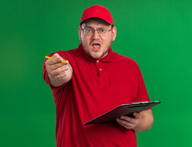 클립 보드와 연필을 들고 광학 안경에 짜증이 과체중 젊은 배달원 복사 공간이 녹색 벽에 격리 가리키는