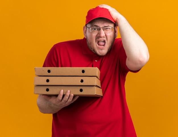 피자 상자를 들고 복사 공간이 오렌지 벽에 고립 된 머리에 손을 넣어 광학 안경에 짜증이 과체중 젊은 배달원