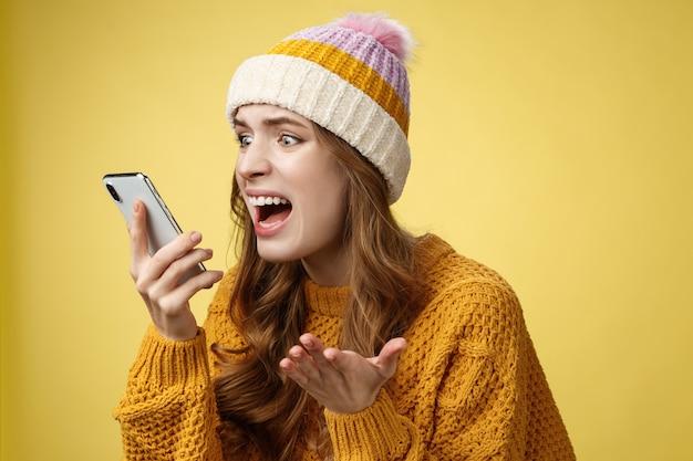 Infastidita incazzata pazza che grida smartphone guarda display vicino al viso irritato che litiga fidanzato rottura tramite telefonata in piedi arrabbiato che urla furiosamente cellulare, alza la mano sgomento
