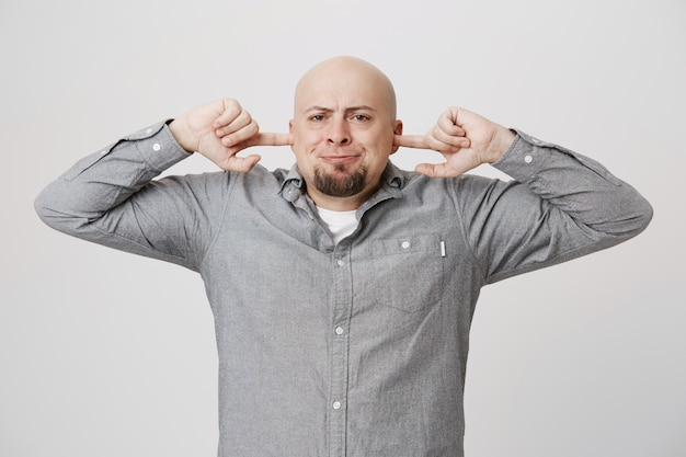 Annoyed pissed-off bald guy shut ears from loud noise