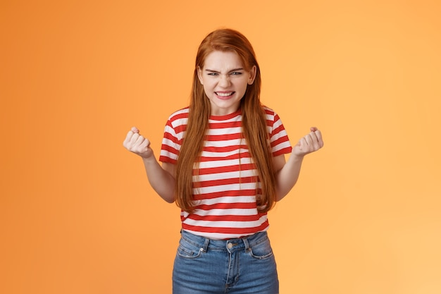 Annoyed pissed redhead female lose competition clench fists angry grimacing evil hateful face pressu...