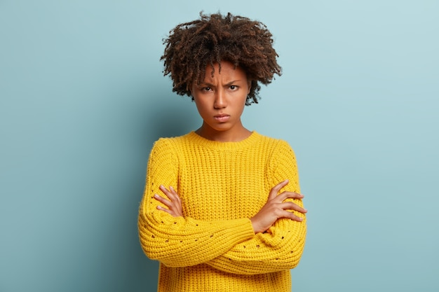 Annoyed pissed woman crosses hands over chest, frowns and sulks, looks from eyebrows, wears knitted yellow sweater, stands against blue wall, feels insulted