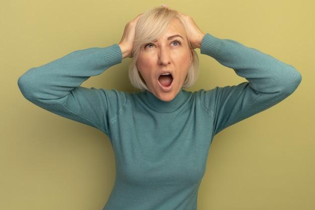 La donna slava abbastanza bionda infastidita mette le mani sulla testa e alza lo sguardo su verde oliva