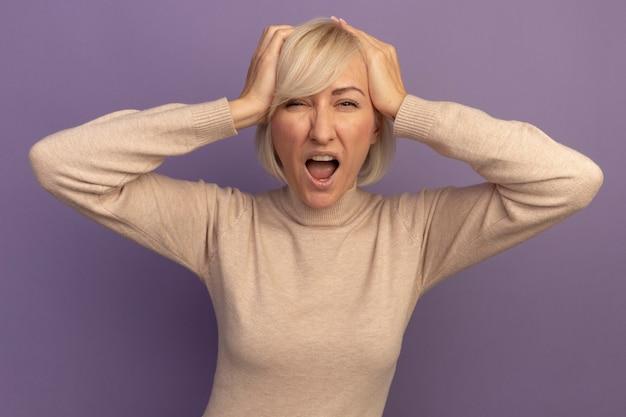La donna slava abbastanza bionda infastidita mette le mani sulla testa sulla viola