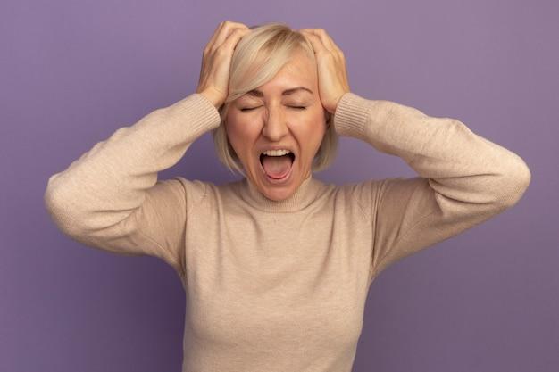 짜증이 예쁜 금발의 슬라브 여자가 머리에 손을 대고 보라색에 비명을 지른다.