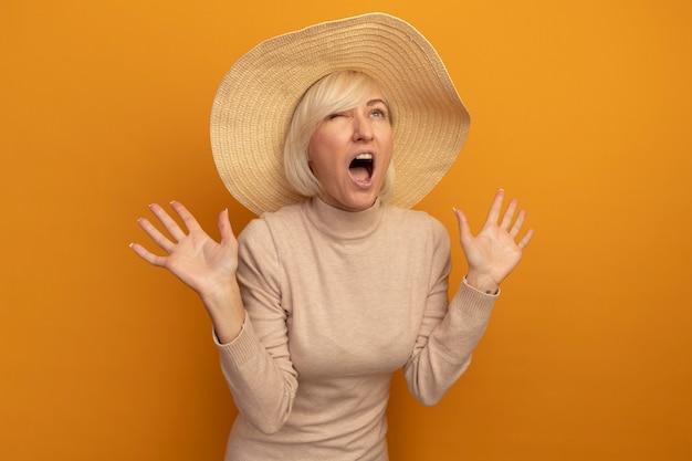 ビーチ帽子をかぶったイライラするきれいな金髪のスラブ女性は、オレンジ色の手を上げて立っています