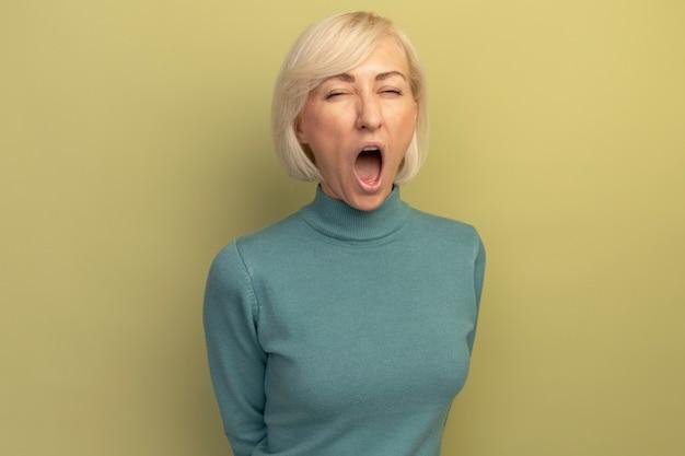 イライラしたかなり金髪のスラブ女性は孤立しているように見える誰かに怒鳴ります