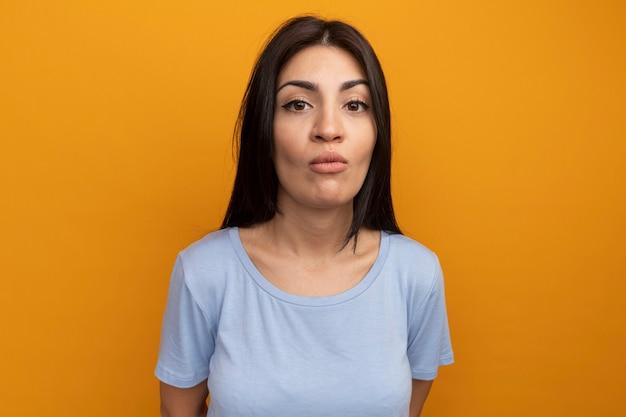 Donna graziosa del brunette infastidita che esamina fronte isolato sulla parete arancione