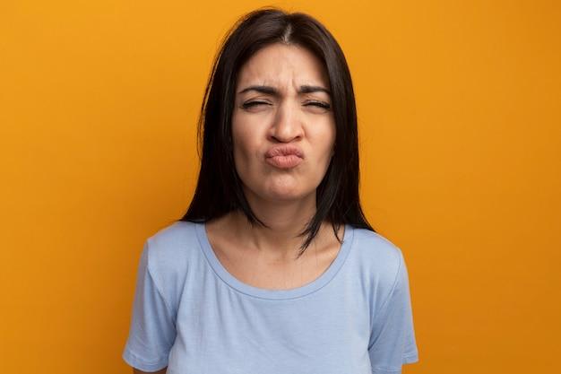 La donna abbastanza castana infastidita esamina la parte anteriore isolata sulla parete arancione