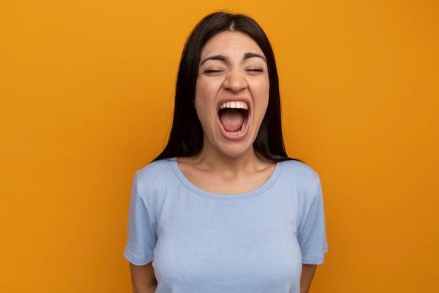 Раздраженная красивая брюнетка женщина кричит изолированной на оранжевой стене