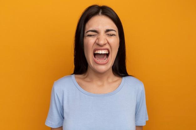 Раздраженная симпатичная брюнетка женщина стоит с закрытыми глазами, изолированными на оранжевой стене
