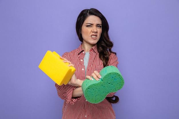 Donna delle pulizie piuttosto caucasica infastidita che incrocia le mani e tiene le spugne