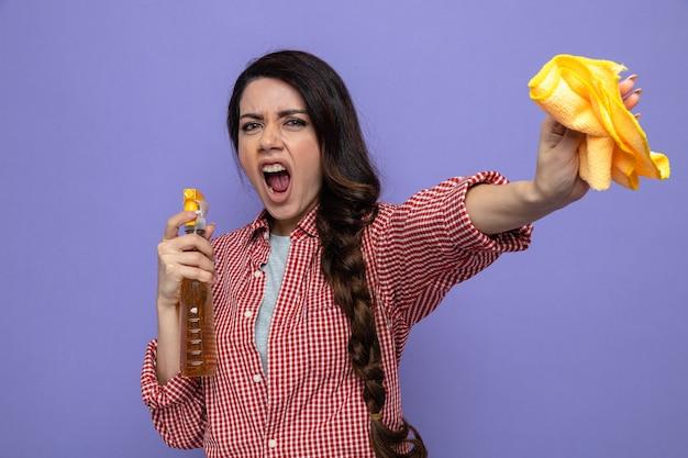 Donna delle pulizie caucasica infastidita che tiene in mano panni per la pulizia e detergente spray