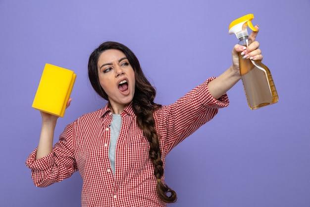 Una donna caucasica piuttosto infastidita che tiene in mano un detergente spray e una spugna che guarda di lato