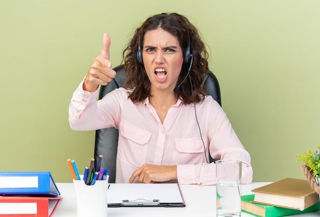 オフィスツールを正面に向けて机に座っているヘッドフォンでイライラするかなり白人女性のコールセンターのオペレーター