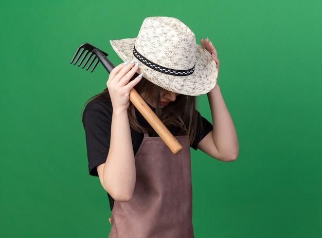 복사 공간이 있는 녹색 벽에 격리된 갈퀴를 들고 정원 가꾸기 모자를 쓰고 유지하는 화난 예쁜 백인 여성 정원사