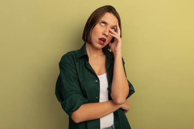 Раздраженная симпатичная кавказская женщина закатывает глаза и кладет руки на лицо на оливково-зеленом