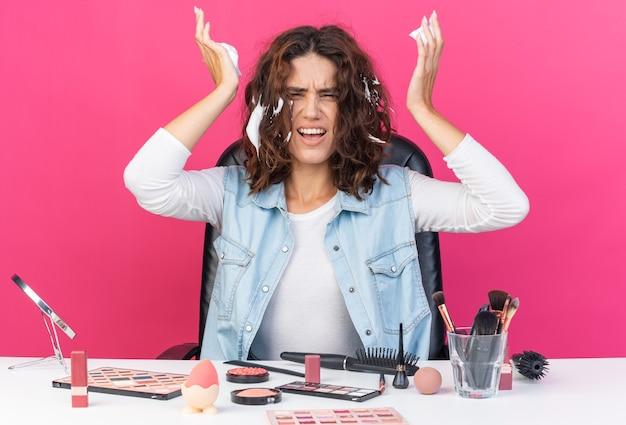 Donna piuttosto caucasica infastidita seduta al tavolo con strumenti per il trucco che applica mousse per capelli isolata sulla parete rosa con spazio di copia