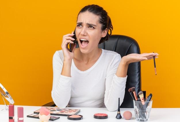 Donna abbastanza caucasica infastidita che si siede al tavolo con strumenti per il trucco che urla a qualcuno al telefono e tiene il pennello per il trucco isolato sulla parete arancione con spazio di copia