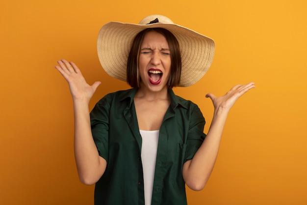 ビーチ帽子をかぶったイライラするかなり白人女性はオレンジ色の手を上げて立っています