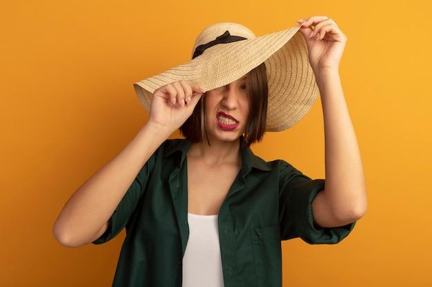 イライラするきれいな女性はオレンジ色の壁に分離されたビーチ帽子で顔を覆います