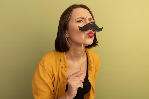イライラするきれいな女性は、オリーブグリーンの壁に隔離された側を見て棒に偽の口ひげを保持します