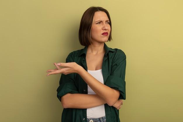 La donna graziosa infastidita tiene la mano aperta e guarda il lato isolato sulla parete verde oliva