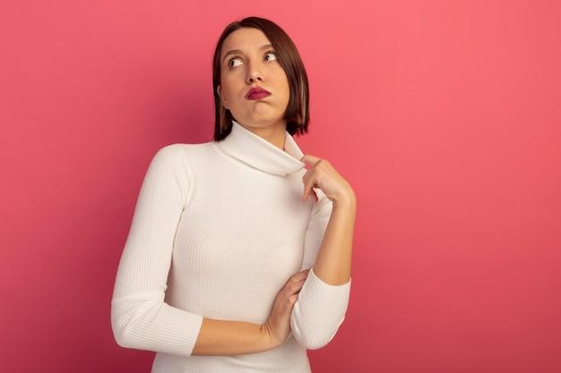 짜증이 예쁜 여자가 분홍색 벽에 고립 된 측면을보고 칼라를 당깁니다.