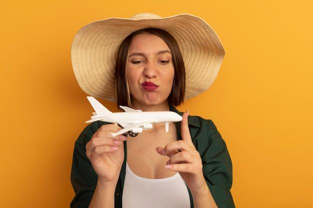 La donna graziosa infastidita con il cappello della spiaggia tiene ed esamina l'aereo di modello isolato sulla parete arancione