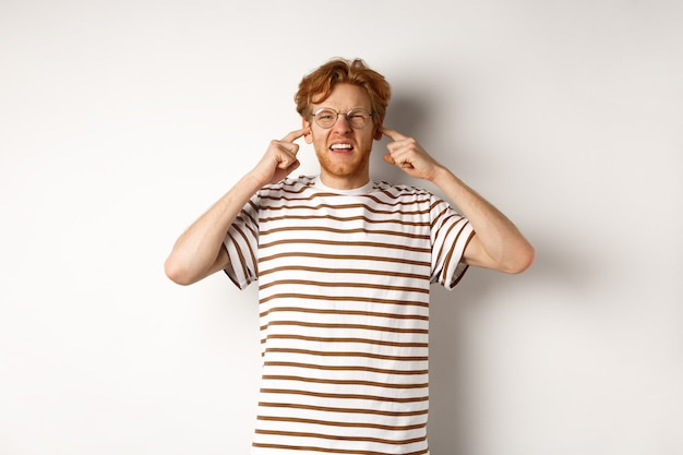Annoyed redhead guy in glasses shutting ears and complaining loud noise, angry at noisy neighbours, standing over white background.